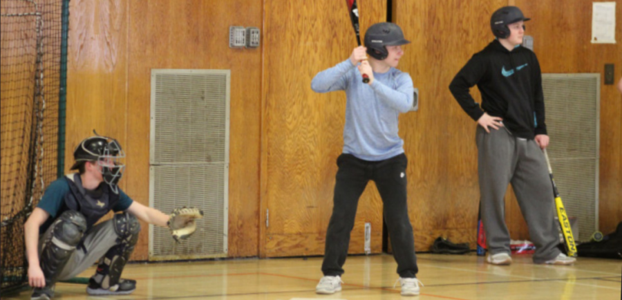 Senior captain Tyler Page steps up to bat in the Bird Middle School gym during the second day of tryouts.