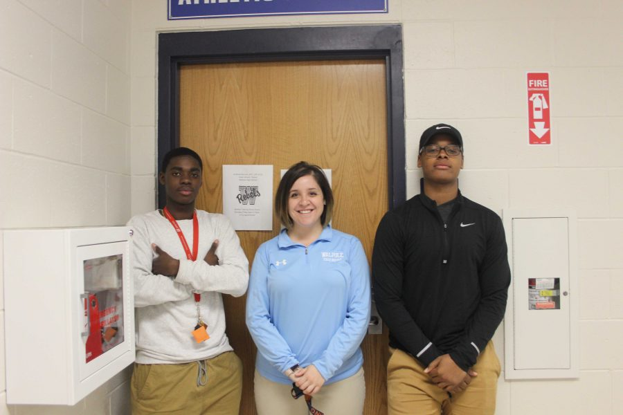 Randall poses outside of her office with students Raynal Louissaint and Reggie Michel.