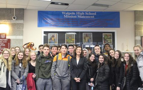 Dr. Bridget Gough stands with students in the Walpole High main lobby under the school mission statement.