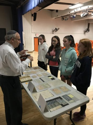 After the presentation, Blechner speaks to 8th grade girls in front of the artifacts he brought.