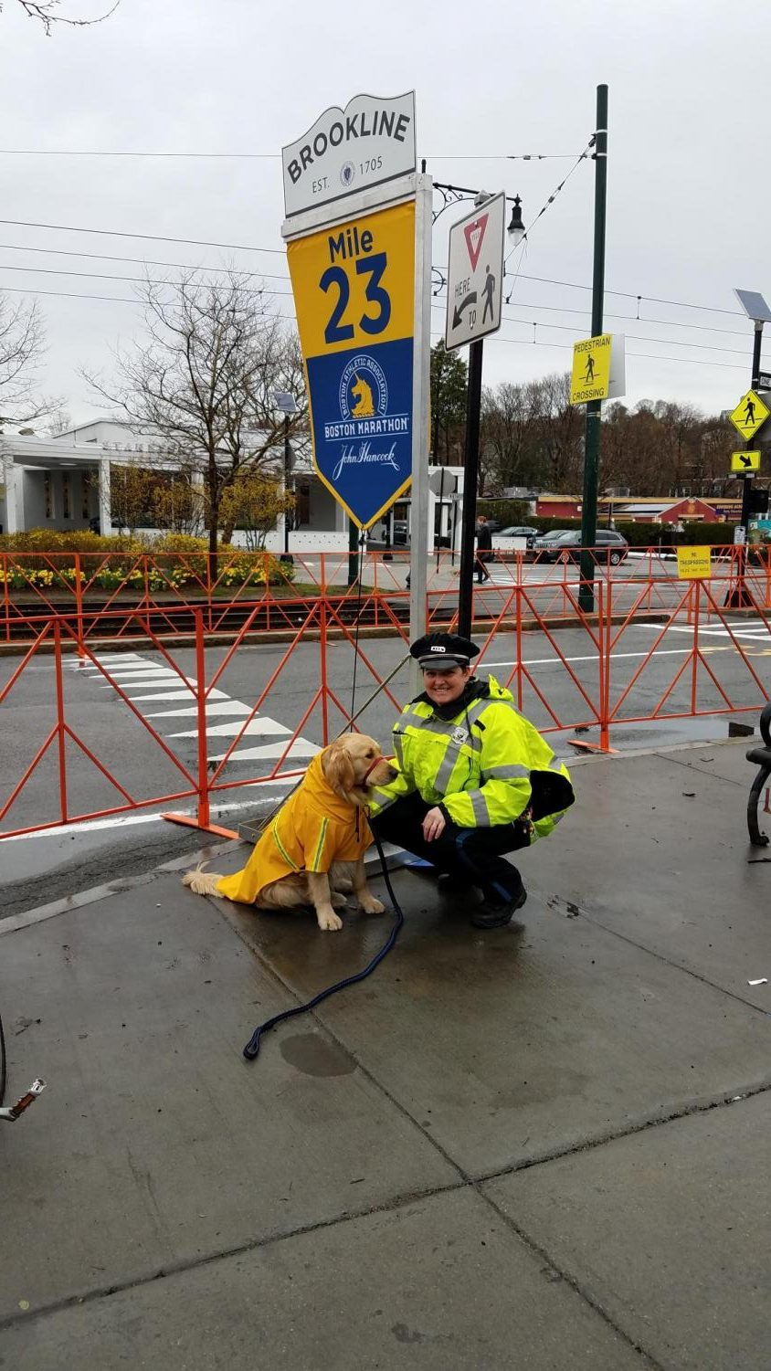 Officer McCabe poses with Rebel's relative, therapy dog Bear, during the Boston Marathon (Photo/Katie McCabe).
