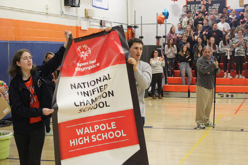 Students carry National Unified Champion banner during the pep rally.