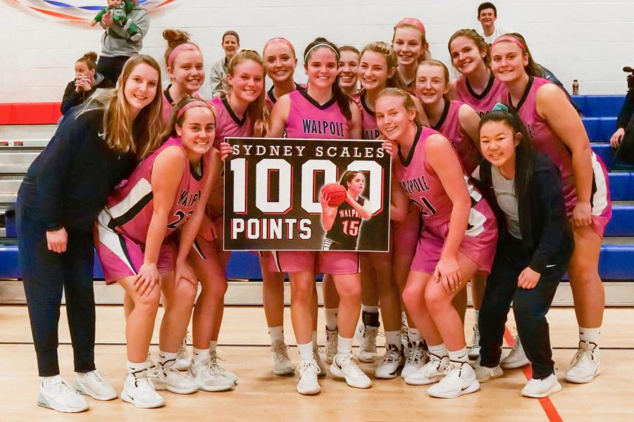 Scales poses with her teammates, holding a poster after scoring her 1,000th point.